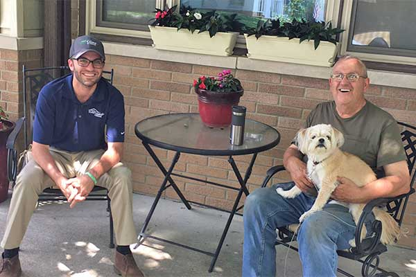 Picture of our expert estimator and a happy Iowa home owner with his dog.