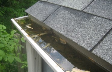 Open faced gutter overflowing and clogged with leaves and debris.