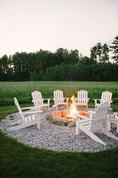 Outdoor fireplace out in the country with yard chairs placed around the lit fire.