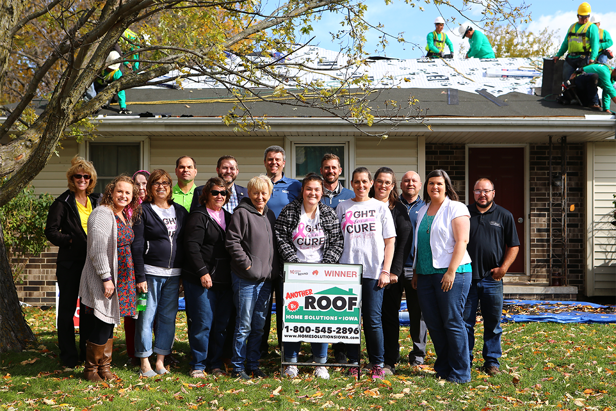 A group photo featuring Home Solutions of Iowa and Tricia, the winner of No Roof Left Behind's contest to receive a new roof.