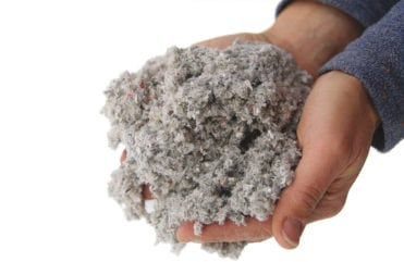 Blown-in cellulose insulation being held in the hands without any protection. It is made up of completely recycled and environmentally safe materials making it an eco-friendly option.