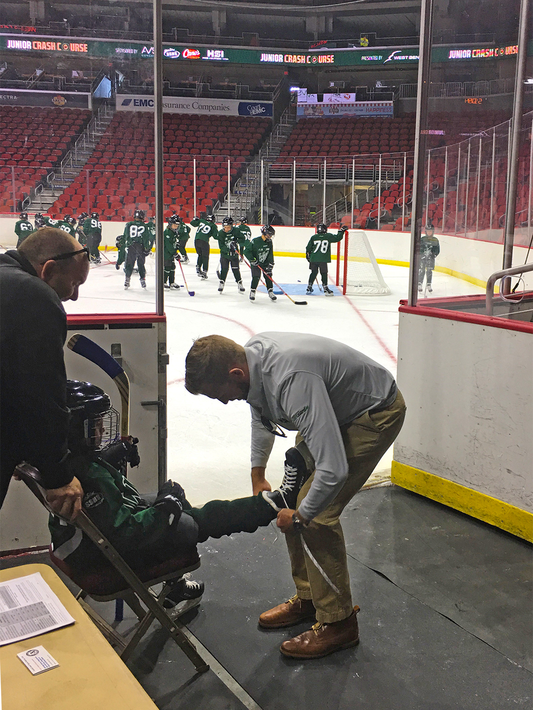 Joe Smith, Owner of Home Solutions of Iowa ties skates for one of the participants of the Iowa Wild Junior Crash Course.