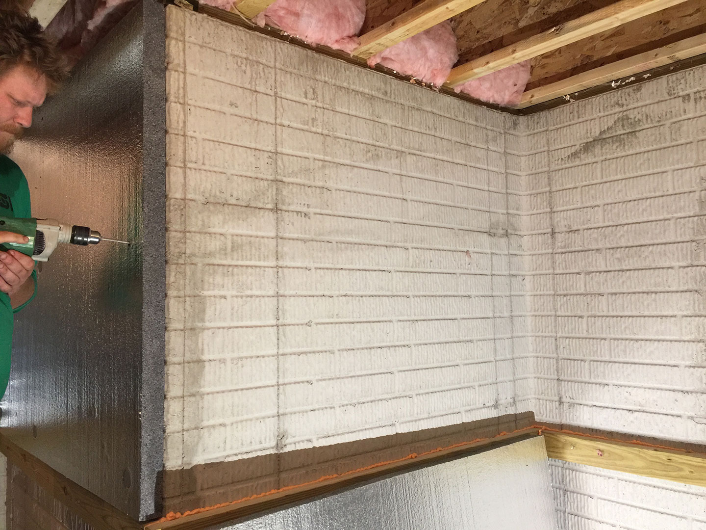 Pictured is during installation of the graphite infused foam insulation. You can also see that the wall has been air sealed along the bottom.
