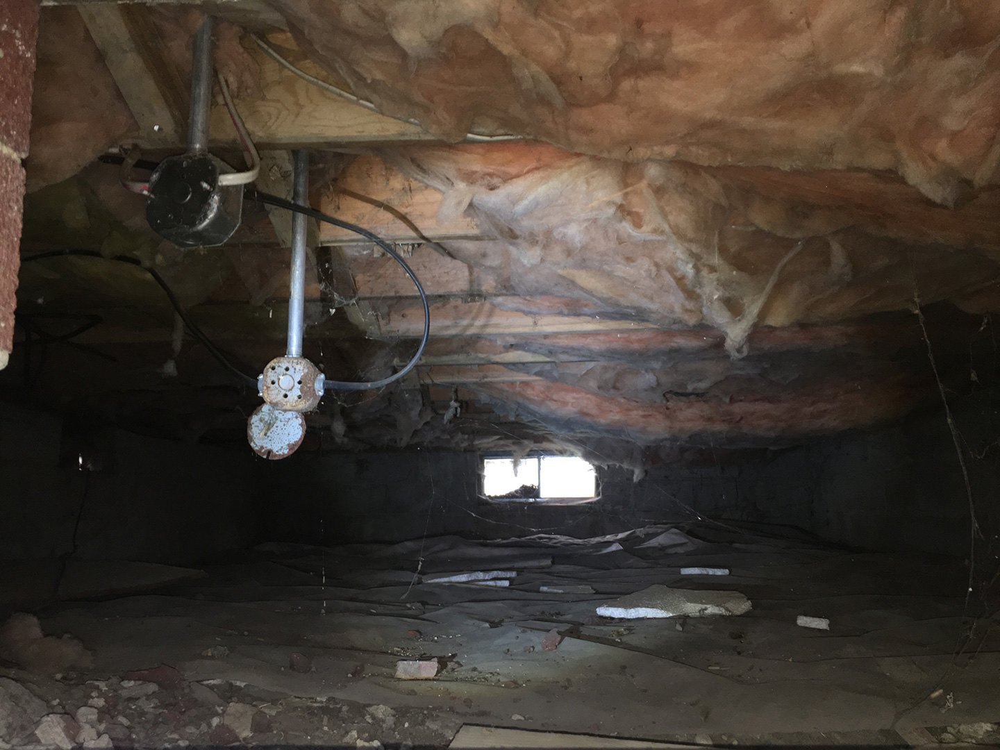 Before image of the crawl space in the basement.