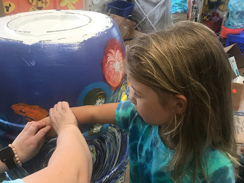 Rain barrel being painted by student