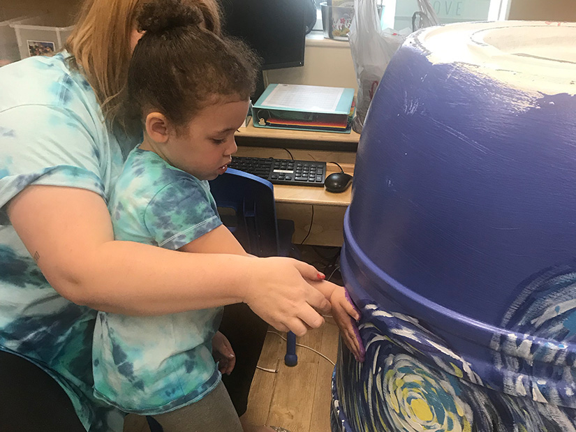 Hand painting a rain barrel