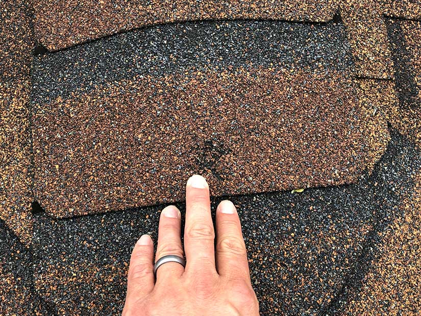 Hail damage to asphalt shingles on a roof in Des Moines, IA.